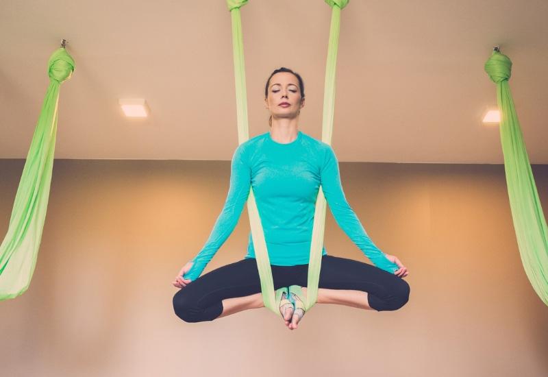 Kvinde yoga i hængekøje og hængekøjer akrobatik
